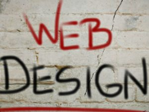 Web design sign painted on brick wall